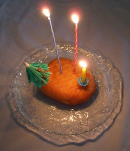 A single donut with birthday candles and paper umbrella decoration.