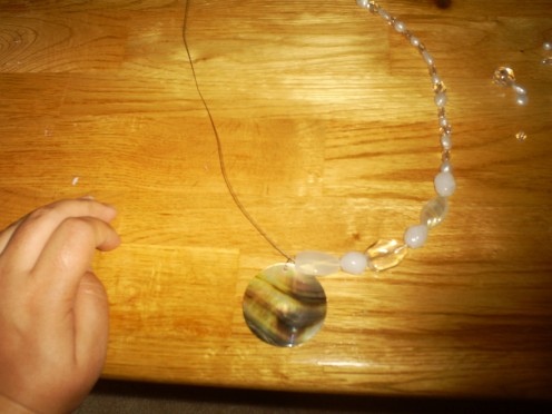 Place the shell in the center of the necklace.