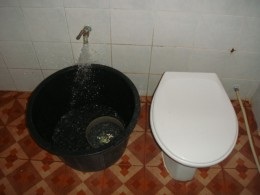"Bathroom or ""Hong Nam"" (Room Water) of a 800 baht bungalow You must dip water from the black tub to flush"
