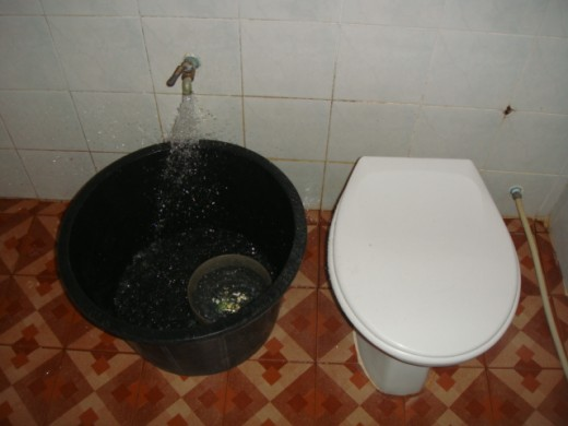 """Bathroom or """"Hong Nam"""" (Room Water) of a 800 baht bungalow You must dip water from the black tub to flush"""