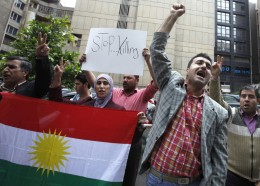 Kurds at a demonstration holding a Kurdish flag