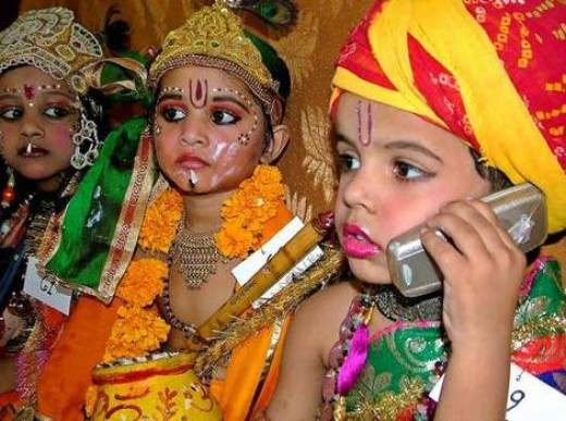 Indian kids as Lord Krishna and Balram talking on the cellphone.