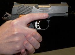 The trigger finger is completely out of the trigger guard and resting alongside the frame of the pistol.