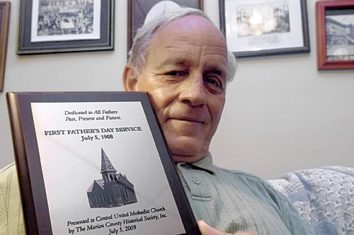 The former pastor of the Central United Methodist Church, the Reverend D.D. Meighan, and the plaque commemorating his 2010 West Virginia History Heroes Award, for his work on behalf of preserving the Fairmont First Fahter's Day History