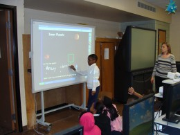 Students interacting with the Promethean Board.