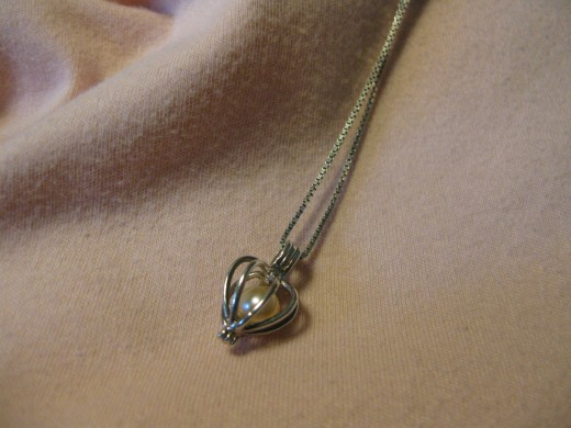 Pink cultured pearl in silver heartshaped cage.