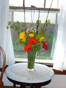 These vibrantly colored Gerber Daisies are the centerpiece in this bouquet. Pussy Willow branches add height.  I would add a varigated Hosta leaf to the inside of this vase to create more interest.