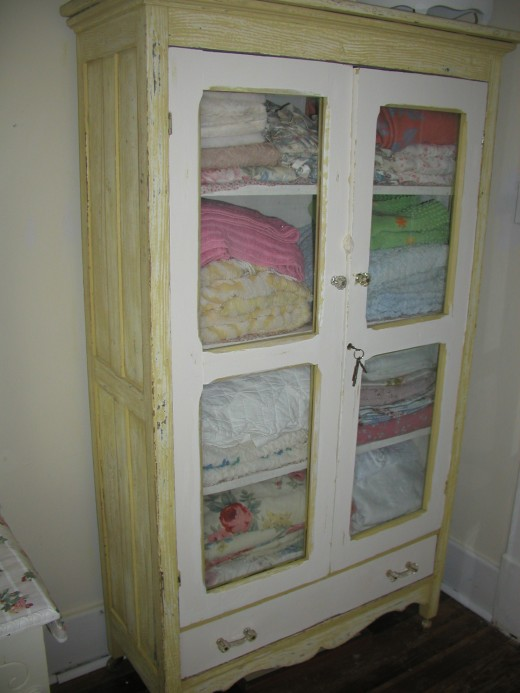 This old cabinet was in the 'dump.'  I pulled it out, paid the $5.00 required and hauled it home. Replaced broken glass, and began sanding/re-distressing, double painting/toning and...here is a Shabby Chic beauty!