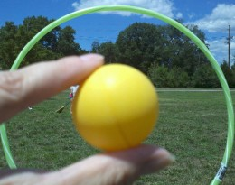 The golden snitch takes a peek from behind a hoop goal post.
