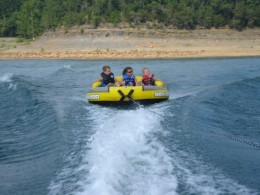Enjoy summer rafting while being pulled behind a larger boat.