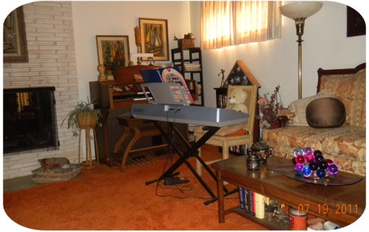 "My living room, where you see George's electronic organ and my Yamaha keyboard.   ""Ludwig von Bearthoven"" keeps the chair warm for me and the little stuffed fawn is my audience.  The open songbook is Show Tunes."