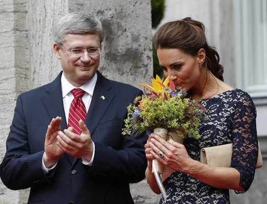 The Duchess smells a bouquet of flowers as Canada's Prime Ministers Stephen Harper looks on during an official welcoming ceremony at Rideau Hall in Ottawa