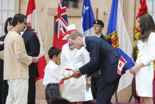 Prince William hands out citizenship flags to newly sworn in Canadian citizens during the Canada Day Citizenship Ceremony at the Canadian Museum of Civilization in Ottawa
