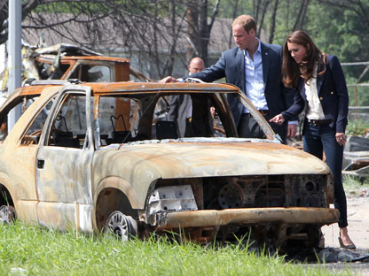 The Duke and Duchess look at a burned-out car in Slave Lake