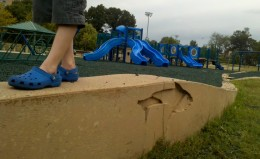 """Balancing on the wall to prevent falling in the """"water"""" as the little kid playground sits in the background."""