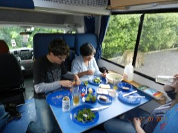 Having lunch inside the camper van. The driver would sit in front next to the navigator and passengers would sit with seat belts once the table is removed. At night the dining area would turn into one of the two doubl double beds for two.