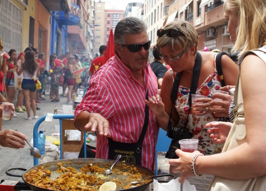 One of the members of a Pea giving visitors  samples of his Peas paella
