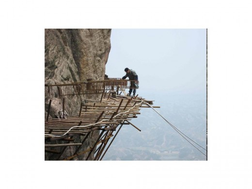 Thousands of metres up the vertiginous slopes of Shifou Mountain in Hunan Province, China,  a team of workers, operating with hardly any safety measures, are building a footpath
