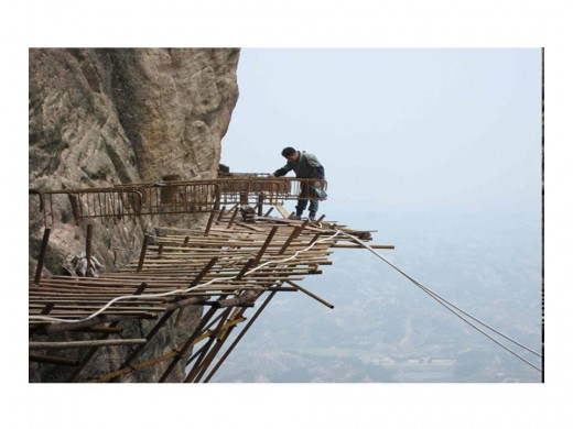 The workers are building a plank road on the side of the mountain that, once it is  finished, will stretch for 3km (9843 ft) and be China 's longest sightseeing footpath
