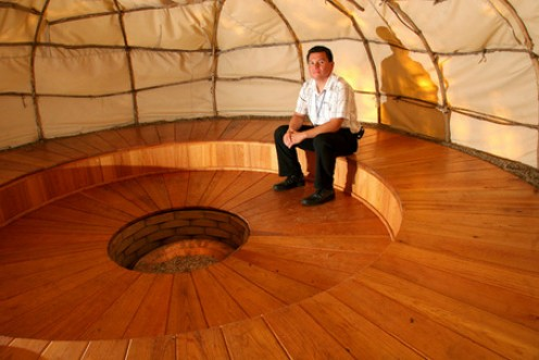 An Oglala Sioux man sits inside a sweat lodge.