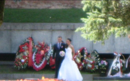 Bride and Groom having wedding photos taken by the Eternal Flame at the Great Patriotic War Memorial inside wall of Kremlin in Veliky Novgorod, Russia.