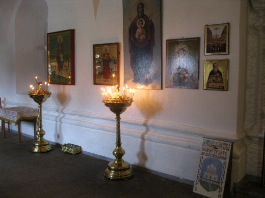 Votive candles and icons inside church.  (Monastery in Valday District near Veliky Novgorod, Russia)