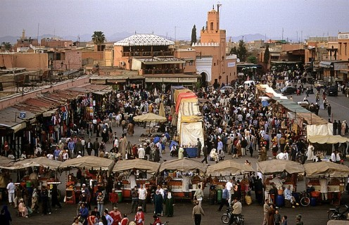Marrakech - Marocco View from Caf Glacier: Place Djamaa el-Fna Background is the Mosquee Quessabine. In front are stands of orange juice seller.