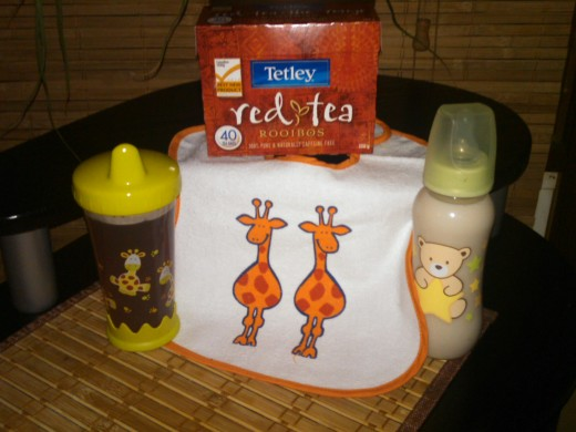 Next to the baby's bib, on the right side is a baby bottle with baby formula and red tea combined. On the left side is a sippy cup with just red tea. I choose giraffes on the bib and cup stating that the red tea is picked from Africa.