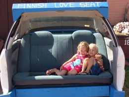 Grace and Alex sitting in the backseat of a car in DaYooper's Tourist Trap.  They call this a 'Finnish Love Seat.'