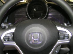 "The paddles are located on the steering column and have ""+"" and ""-"" symbols on them. They toggle easily when pulled forward."