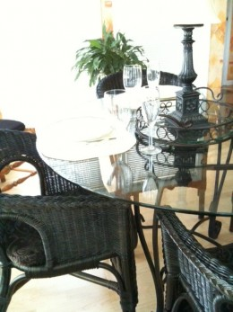 Repainted and repurposed wicker chairs moved to sunny breakfast nook for a cheap decorating idea.