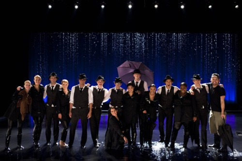 A group shot of the group when performing the mash-up of Umbrella/Singing in the Rain including umbrellas, a rain machine and Gwyneth Paltrow.