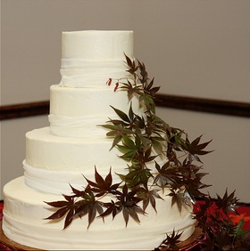 This was a simple four-tier round layered cake I made about three years ago.  The border was layered with very fine material similar to lace and a cascade of Japanese Maple adorned the cake on one side.  It was simple, but elegant.