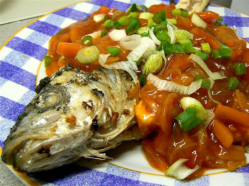 escabeche with onion leaves topping