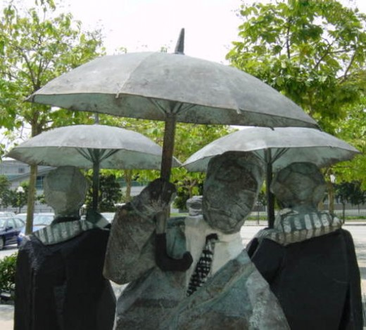 Businessmen with umbrellas, sculpture near Fullerton Hotel, Singapore