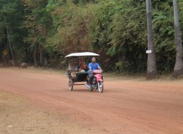 Tuk-Tuk driver & visitor travel through the thick, luscious jungle that surrounds the Temples of Angkor