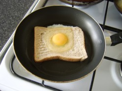 The egg is carefully poured on to the bread so that the yolk slips in to the hole