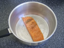 Salmon fillet is laid skin side down in a pot and seasoned with salt, white pepper and dried dill