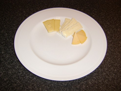 Cheeses are sliced and added to a serving plate