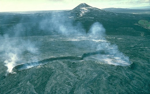 Kupaianaha lava lake in foreground, Pu'u O'o in background, 1990. In 1991-1992, Kupaianaha drained and died, and a lava pond returned to Pu'u O'o's summit crater.