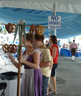 Pretty German girl sells hot pretzels with flair.