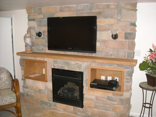Incorporating a fireplace into the entertainment center design maximizes space and gives the room a warm feel.
