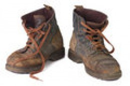 MENS OLD WORK BOOTS. WORN, DIRTY, LOTS OF HOLES. WORN BY BLUE COLLAR LABORERS WHO NEVER GET RAISES FOR THEIR JOBS OF SHOVELING WASTE MATERIAL FROM A JOB SITE.