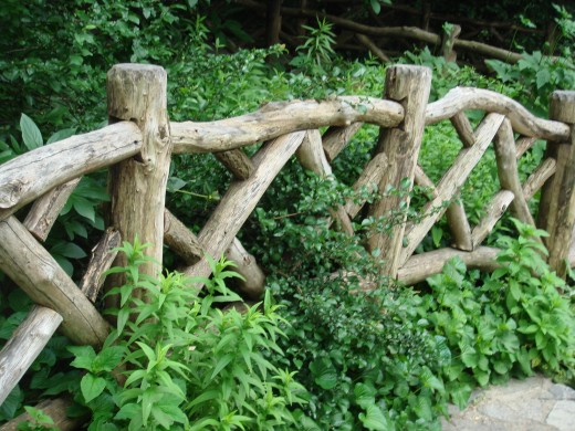 Carved wooden fence that loops throughout the walkways of Shakespeare Garden.
