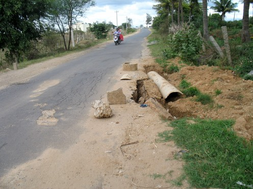 THIS ROAD WAS REPAIRED JUST UNDER 6 MONTHS DURING REPAIR THE CONTRACTOR RAN HIS ROAD ROLLER OVER A WATER PIPE AND IT MADE A PIT.WE HAVE PIT STOP HERE.WHEN IT WILL BE REPAIRED,AFTER ELECTION TO PANCHAYATS.