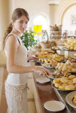 WE DON'T BLAME THIS YOUNG WOMAN FOR TAKING HER TIME--CHOOSING GOOD FOODS FROM THIS ALL-YOU-CAN-EAT-BUFFET.