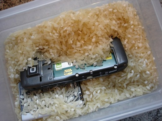 An example of a cellphone with SIM and battery removed, submerged in rice.
