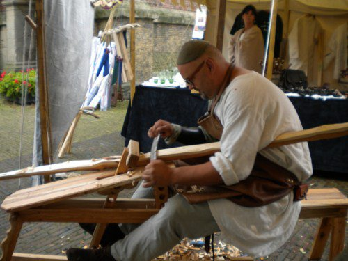 Magen Klomp working on a bow at a Medieval Fair, which he attends regularly with his company Fairbow or as Chairman of the Dutch Warbow Society.