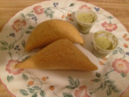 A pair of empanadas with green chili sauce