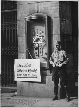 """On April 1, 1933, the boycott which was announced by the Nationalsocialistic party began. Placard reads, """"Germans, defend yourselves, do not buy from Jews"""", at the Jewish Tietz store. Berlin. New York Times Paris Bureau Collection."""